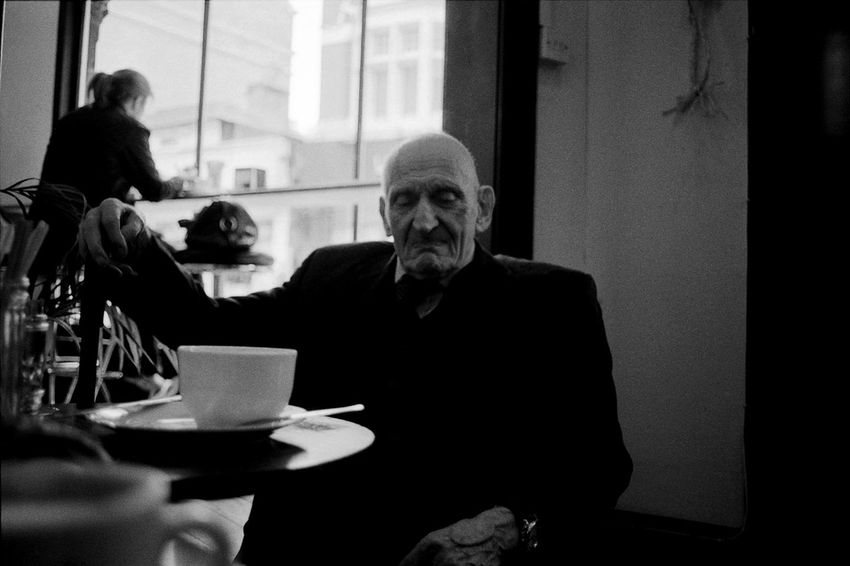 Old Man with Coffee Cup Boys Casual Clothing Documentary Style Photography Elementary Age Food And Drink Front View Holding Indoors  Leisure Activity Lifestyles Looking At Camera Old Man Person Portrait Portraiture; B/W Photography Reportage Street Photos Taking Fotos Images Photographic Camera Lens Architectural Design Building Structual Support Detail Of Tower Block In Sunshine Blue Sk Sitting Table Waist Up Young Adult Young Men