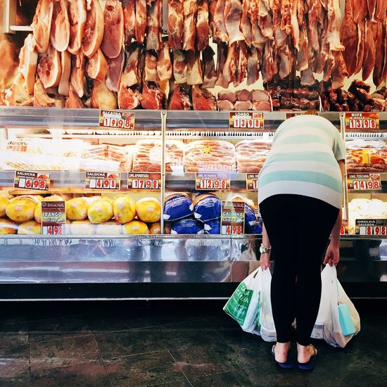 Rear View Of Woman Bending Against Store