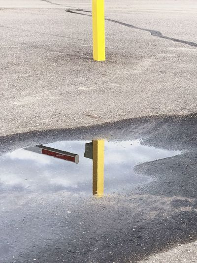 Pin. Yellow Street Asphalt Road No People Day Bollard Puddle Puddle Reflections Reflection Reflection_collection Sign City Communication Warning Sign Water Direction Safety Guidance Dividing Line