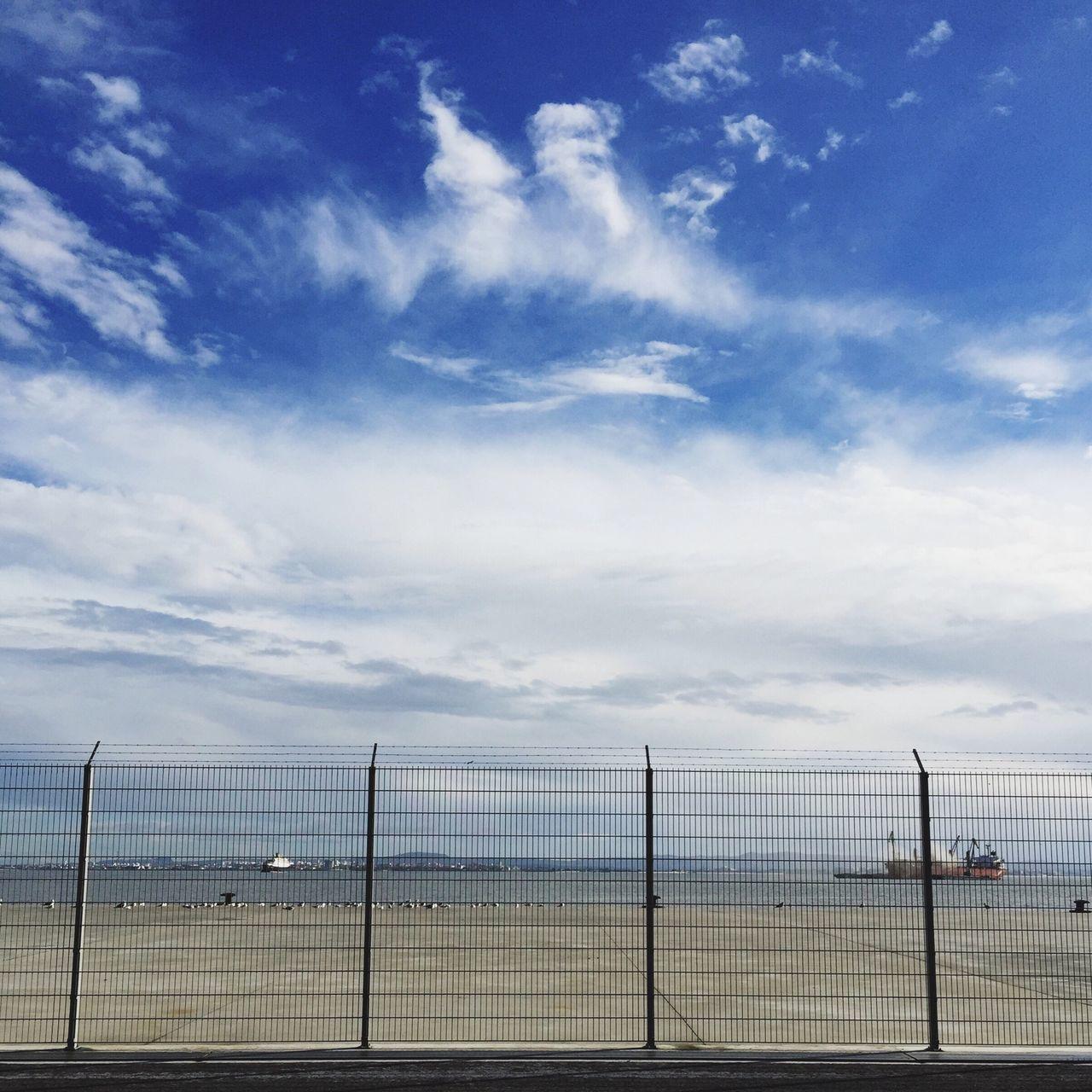 Fence On Harbor Against Sky