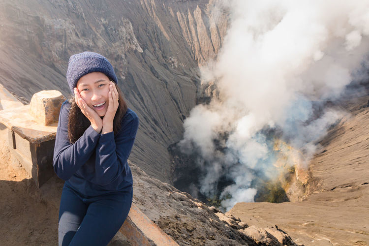Portrait Of Young Woman With Hands On Chin Sitting By Bromo Crater