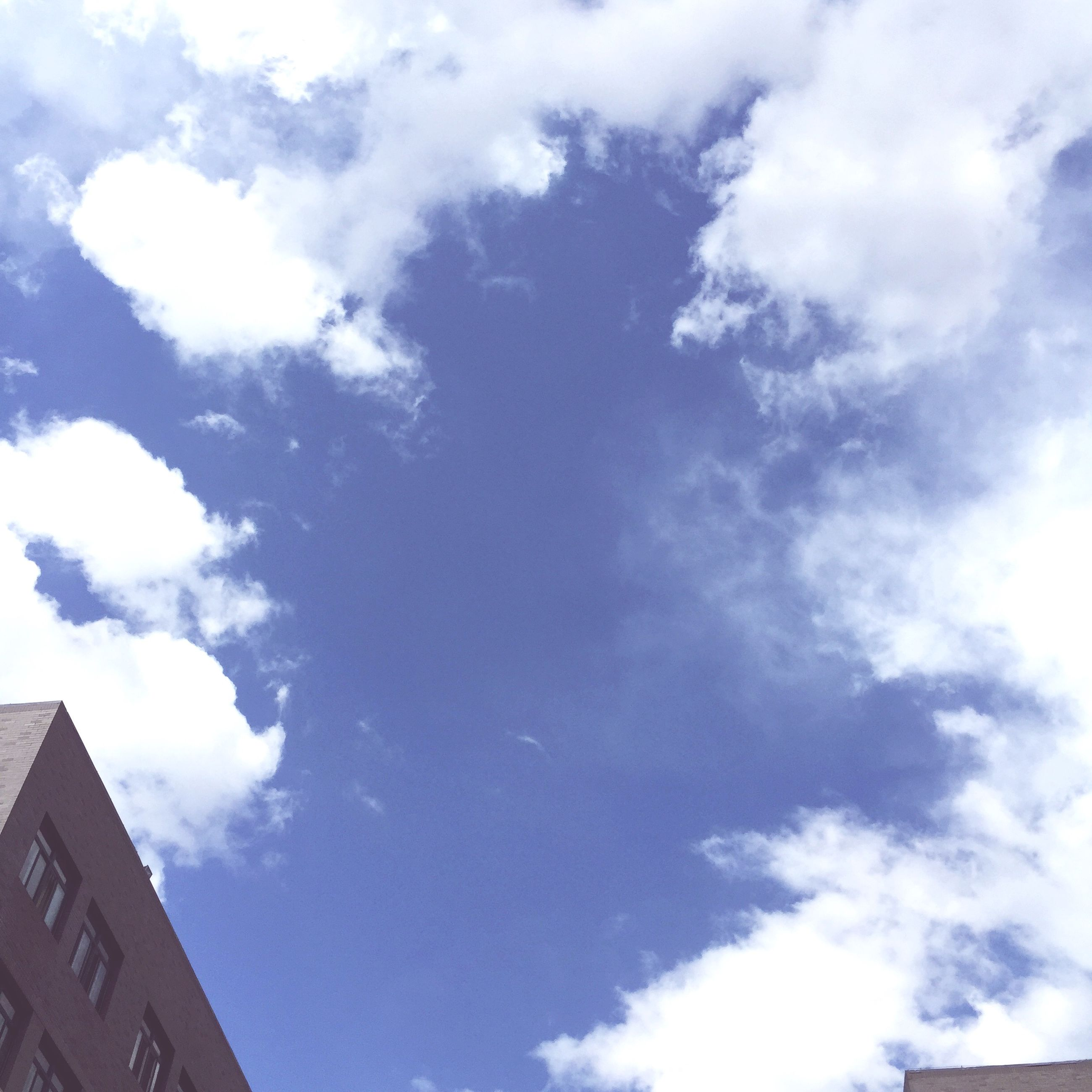 low angle view, sky, building exterior, architecture, built structure, cloud - sky, cloud, cloudy, high section, blue, building, city, outdoors, day, no people, nature, residential building, sunlight, residential structure, tall - high