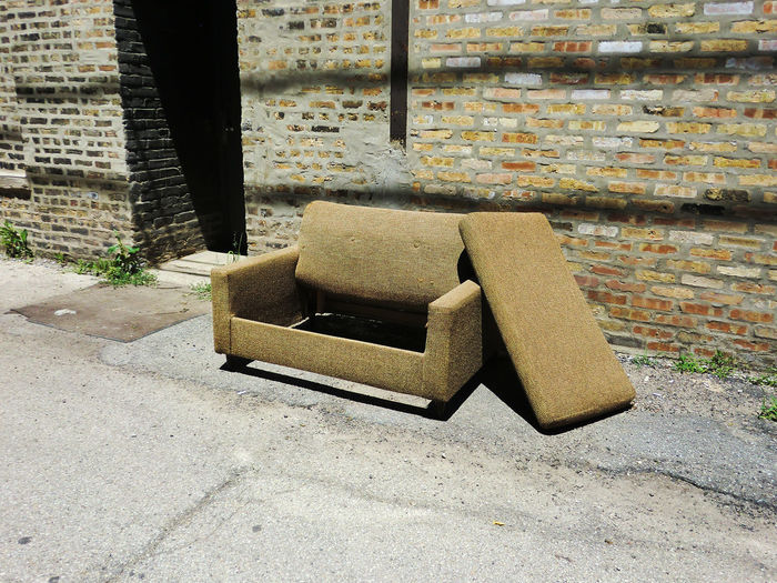 Abandoned Armchair On Footpath Against Building During Sunny Day