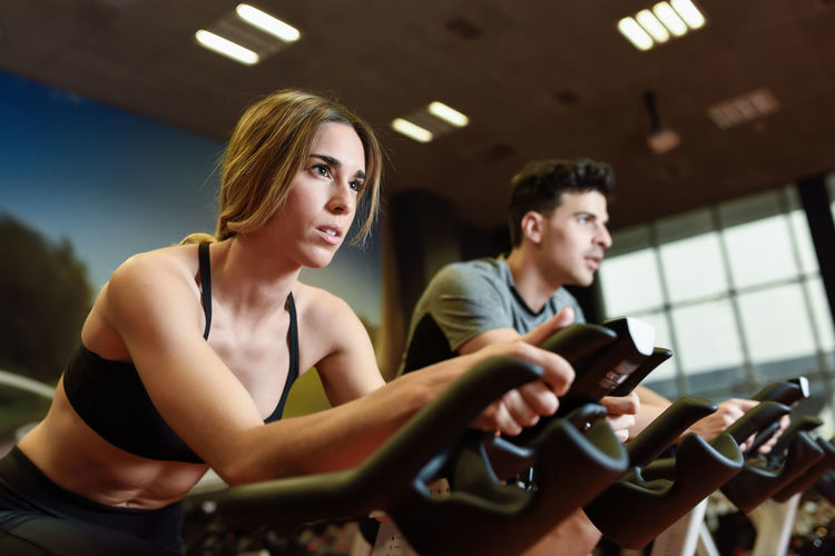 Young man and woman biking in the gym, exercising legs doing cardio workout cycling bikes. Two people in a spinning class wearing sportswear. Exercising Adult Adults Only Cycling Cyclo Indoor Gym Healthy Lifestyle Indoors  Leisure Activity Lifestyles People Sitting Spinning Women Young Adult Young Men Young Women