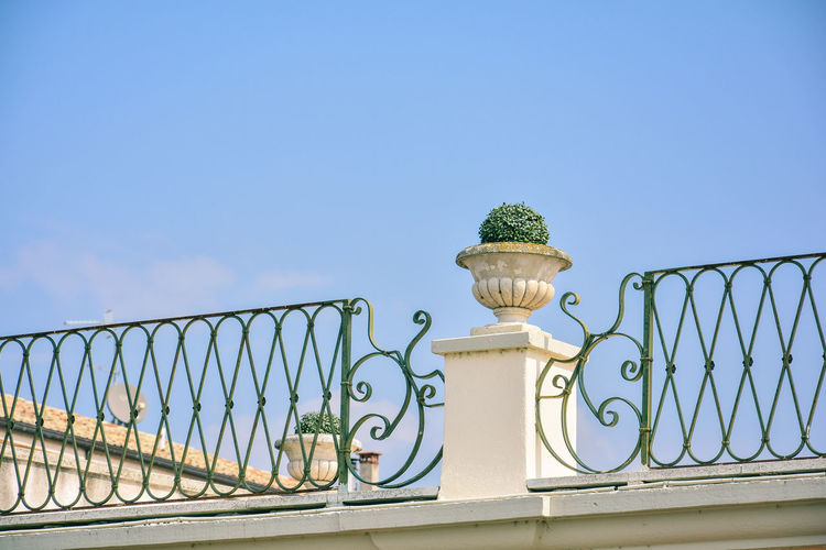 Low angle view of metal railing against blue sky