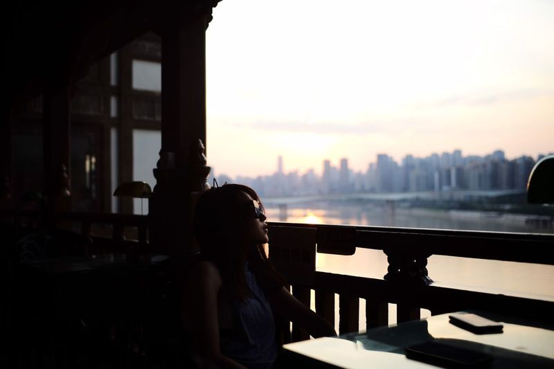 Portrait of woman sitting in city against sky during sunset