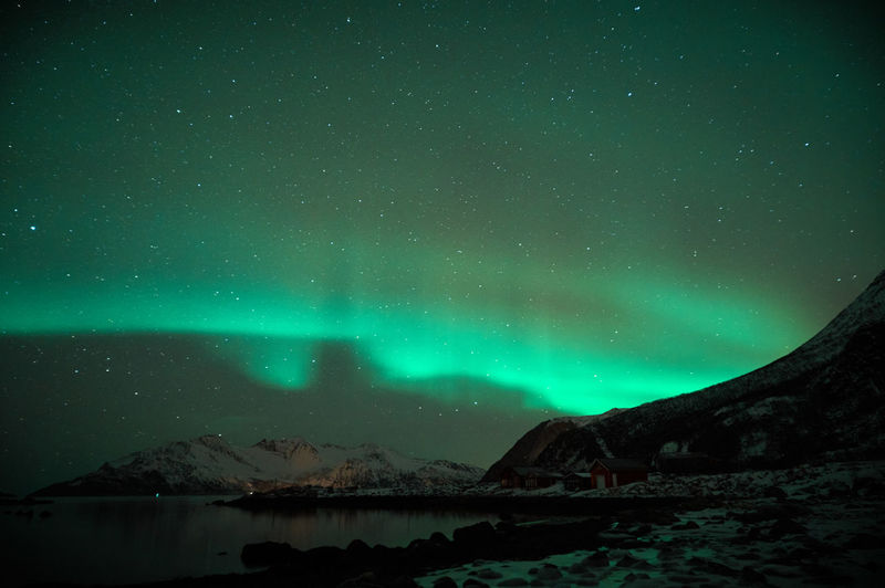 Scenic view of snowcapped mountains and northern lights against sky at night