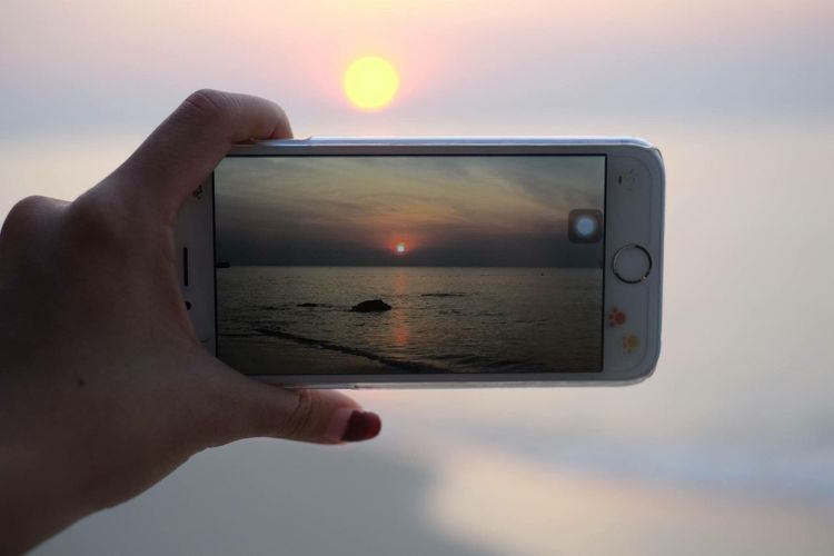 Mobile Conversations Human Hand Human Body Part Sea Sunset Photography Themes Holding Personal Perspective One Person Sky Close-up Device Screen Beach People Adults Only Horizon Over Water Sun Adult Outdoors Digital Viewfinder Day