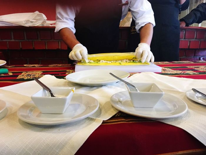 Midsection Of Chef Preparing Food At Table In Restaurant