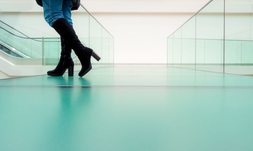 Low section of woman standing on glass floor
