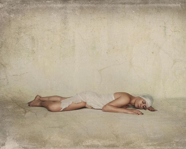 Mature woman sleeping on floor against wall
