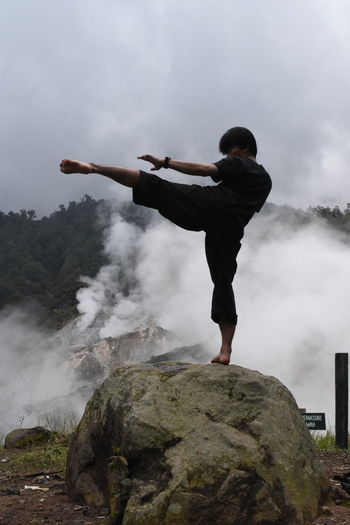 Young man practicing karate on rock formation in foggy weather