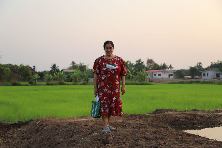 Portrait of women standing on field against clear sky