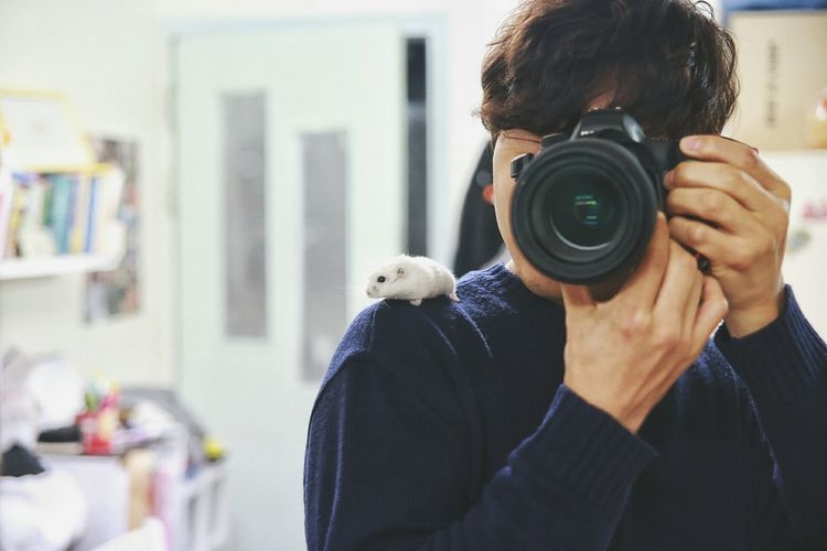 Rat on shoulder of woman photographing through slr camera at home