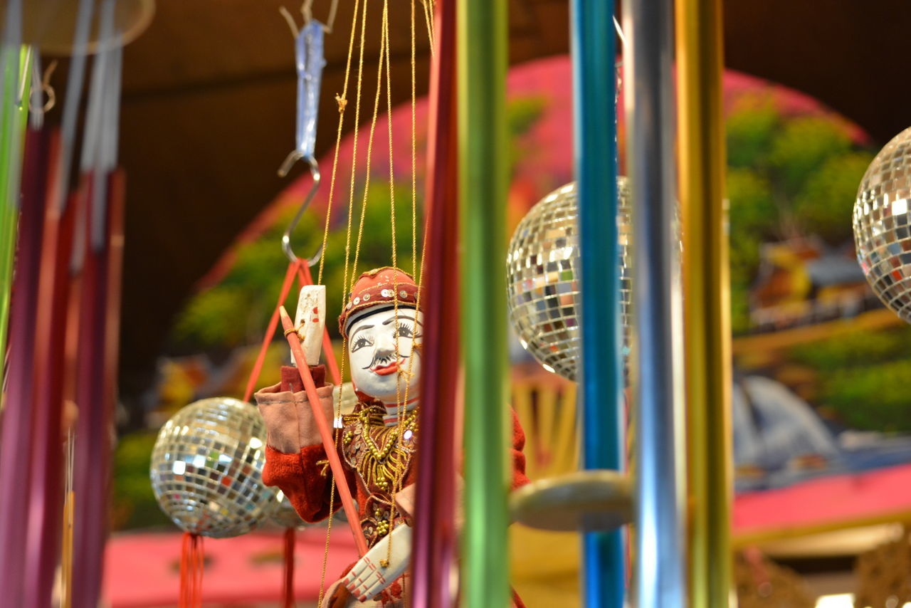 no people, focus on foreground, multi colored, hanging, close-up, day, outdoors, carousel