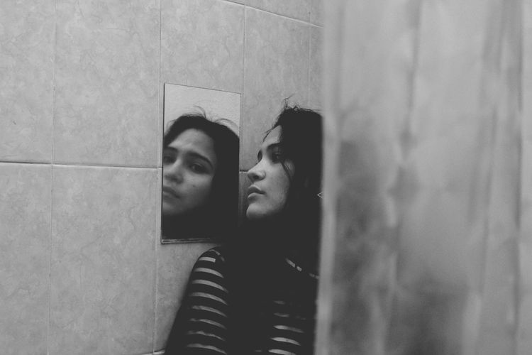 Young woman looking at mirror in bathroom