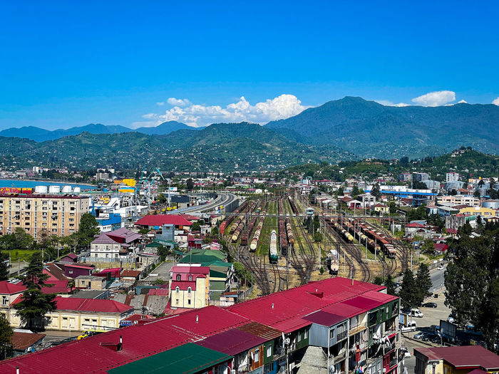 High angle view of townscape and mountains against blue sky
