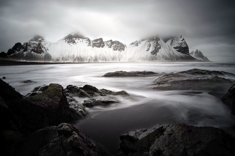 "Another shot from Vestrahorn and it seems heavy storm is coming! It will be enough for a finalist in next ""The Great Outdoors""...? EyeEm Best Shots EyeEm Nature Lover EyeEmNewHere Iceland Landscape_Collection Long Exposure Shot The Great Outdoors - 2018 EyeEm Awards Winter Adventure Beauty In Nature Cloud - Sky Flowing Flowing Water Landscape Long Exposure Mountain Nature No People Power In Nature Rock Scenics - Nature Sea Sky Snowcapped Mountain Water"