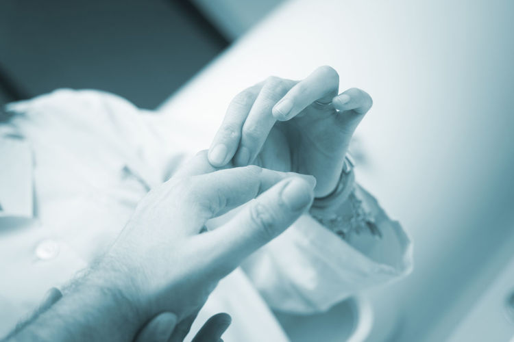 Midsection of doctor holding patient injured finger at hospital