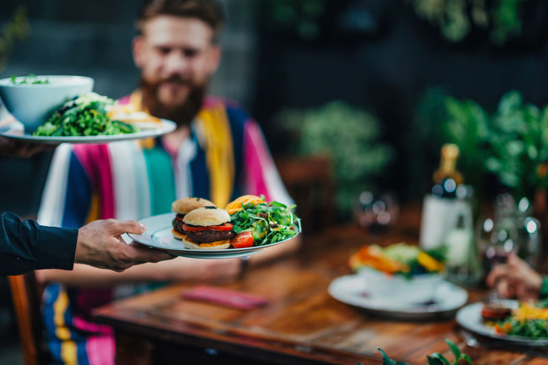 Cropped Hand Of Waiter Keeping Food On Table In Restaurant