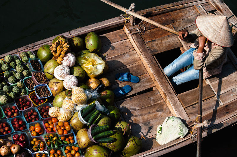 High Angle View Of Person Selling Fruits And Vegetables On Boat In River