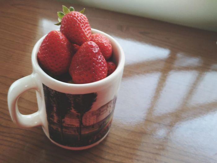 Close-up of strawberries in cup on table