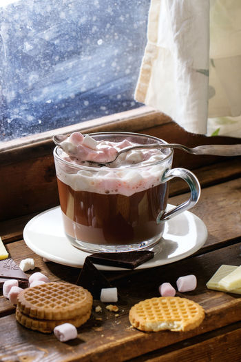 Glass cup of Hot chocolate with marshmallows and cookies, chopping chocolate and mittens over wooden window sill near window in sunny day. Rustic style. Beverage Chocolate Coffee Dessert Marshmallow Pink Rustic Wintertime Drink Foam Food And Drink Foodphotography Glass Hot Chocolate Hot Drink Mug Sweet Sweet Food Table Window Window Sill