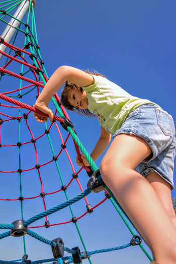Low angle view of cute girl climbing on rope pyramid against clear blue sky