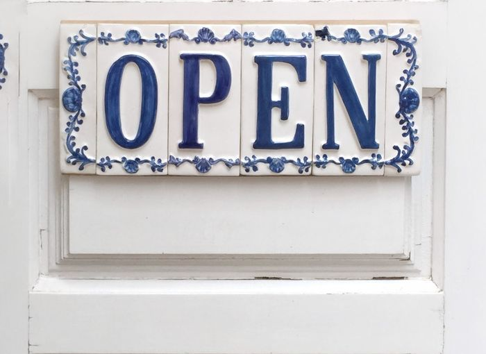 Close-up of open sign on white door