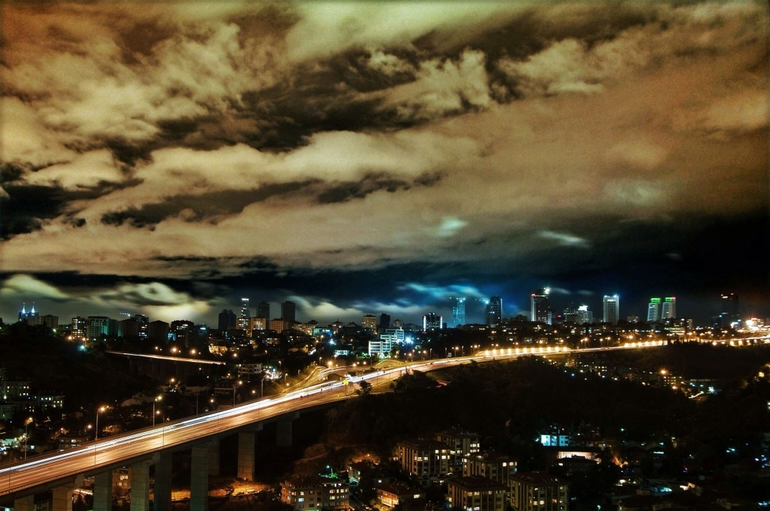 illuminated, city, architecture, cityscape, built structure, building exterior, night, sky, cloud - sky, crowded, cloudy, high angle view, city life, residential district, residential building, dusk, storm cloud, outdoors, residential structure, weather