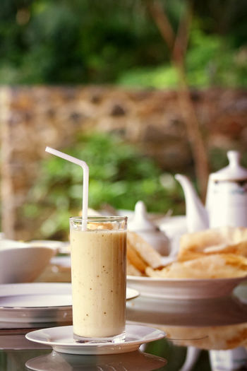 I am really into sri lankan banana milkshakes for breakfast Reflection Breakfast Time Breakfast Table No People Beverage Focus On Foreground Bananashake Banana Shake Breakfast Drink Drinking Glass Drinking Straw Table Close-up Food And Drink Milkshake Frothy Drink Froth Milk Saucer
