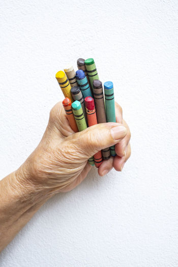 Senior woman's hand holding multi colour crayon isolated on white background Art And Craft Creativity Hoppy Art Body Part Choice Close-up Crayon Finger Grandma Grandmother Hand Holding Human Body Part Human Hand Multi Colored Old Woman One Person Paintbrush Painting Senior Women Stationary Wall - Building Feature White Background Wrinkled