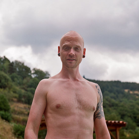 Portrait Of Shirtless Man With Tattoo Standing On Mountain Against Sky