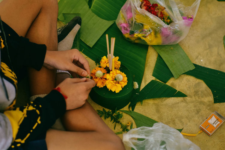 High angle view of woman sitting by religious offering