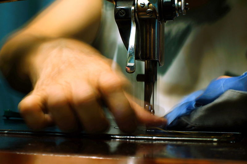 Cropped image of tailor stitching on sewing machine