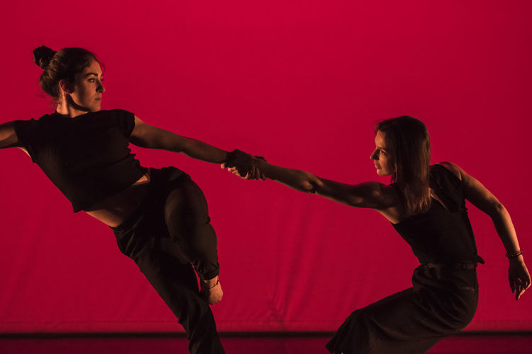 Contemporary dancers in balance during the performance Adult Art Balance Ballet Ballet Dancer Black Dress Contemporary Dance Cooperation Coordination Dance Dancer Dancers Dancing Flexibility Indoors  People Performance Red Skill  Teamwork Togetherness Two People Women Young Adult Young Women