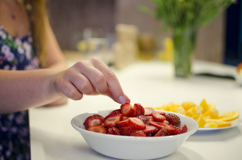 Midsection of woman touching chopped strawberries