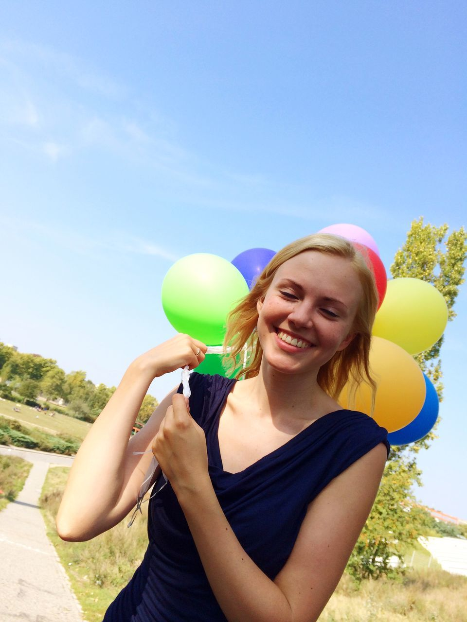 Cheerful Woman With Balloons Standing At Park Against Blue Sky