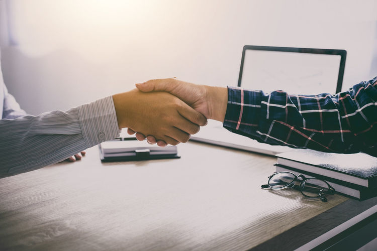 Midsection Of Businessmen And Colleague Shaking Hands At Office