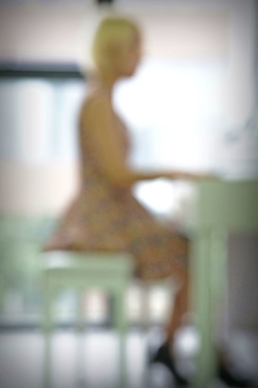REAR VIEW OF WOMAN STANDING BY BLURRED MOTION