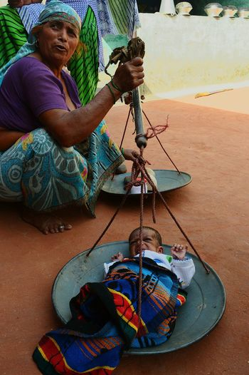 Senior woman measuring baby girl on weight scale
