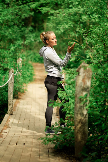 Side View Of Young Woman Standing On Boardwalk In Forest