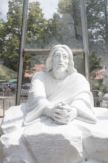 Statue of man sitting against white wall