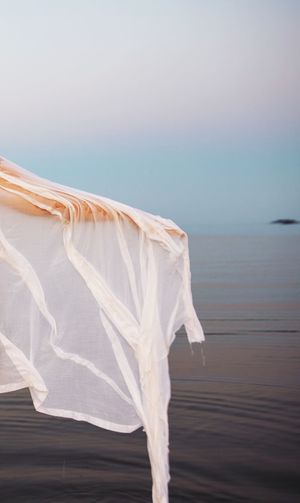 Arm in white fabric in front of water