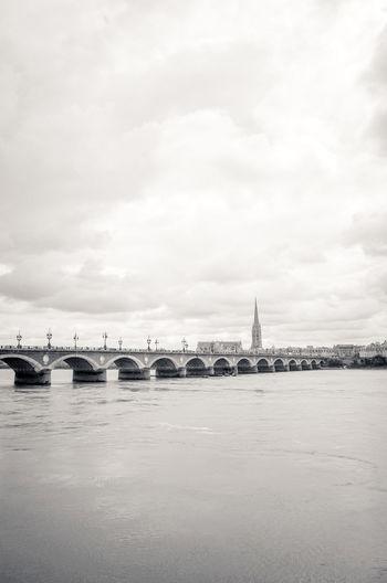 Pont de pierre bridge over river against cloudy sky