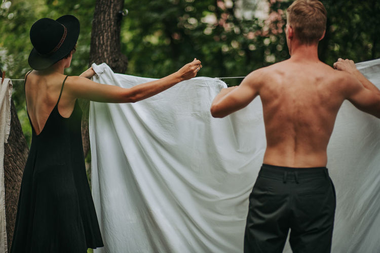 Rear view of shirtless man and woman standing against plants