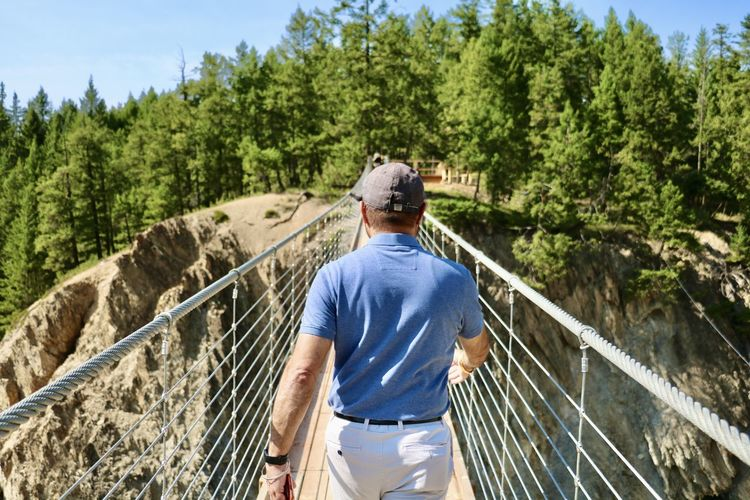 Rear view of man leading the way by railing of suspension bridge against trees