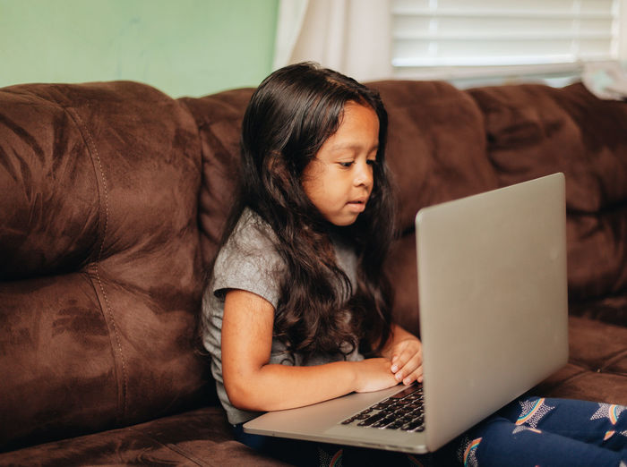 Mixed race young girl at home on the sofa using a laptop computer for learning