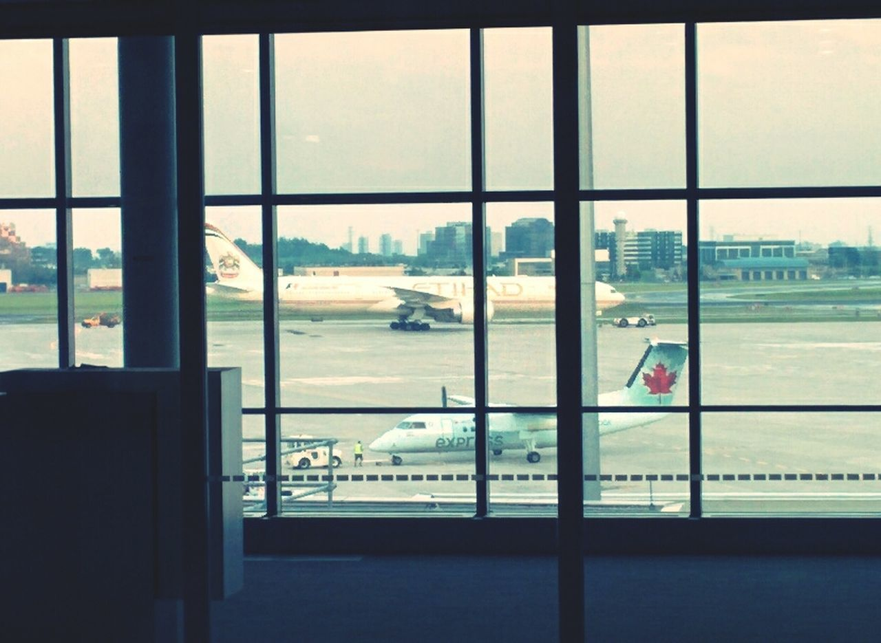 window, transportation, glass - material, indoors, airport, airplane, looking through window, day, no people, travel, sky, air vehicle, airport runway, built structure, runway, architecture, airport departure area, city, close-up, nature, cityscape