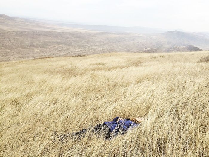 Scenic View Of Woman Lying In Field Against Sky